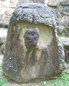 A standing stone with a large carved niche apparently representing the mouth of a monstrous creature, with its eyes carved onto the upper portion of the monument. The niche is occupied by a badly eroded figure depicted from the waist up. The figure has its right arm raised and with traces of a helmet on the figure's head.