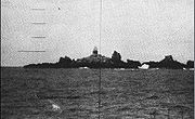 Large multiple rock outcroppings located in the middle of the ocean with a lighthouse located in the center as seen through a submarine periscope.
