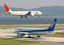 A white and red-tailed Japan Airlines aircraft above runway, with landing gears down, and an All Nippon Airways in blue and white livery taxiing
