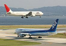 Uma aeronave da Japan Airlines de cauda branca e vermelha acima da pista, com trens de pouso abaixados, e um All Nippon Airways em libré azul e branco taxiando