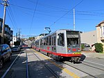 Outbound train at 15th Avenue and Taraval station, February 2019.JPG