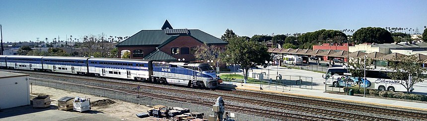 Northbound Surfliner pulling into station where a regional bus is parked and a local bus boards passengers at the covered island platform