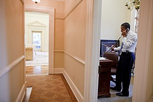 Barack Obama in the Oval Office Study; the interior of the Oval Office can be seen through the open door