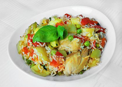 Parboiled rice with chicken, peppers, cucurbita, peas and tomato.