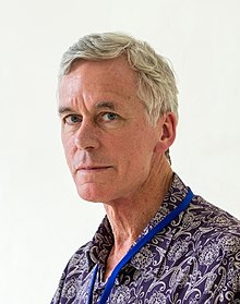 A picture in profile of a man with grey hair. He is wearing a purple batik shirt.