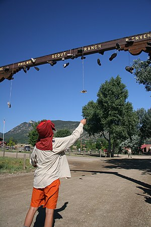 Shoe tossing - A Boy Scout throws his boots over the Philmont entrance sign at Base Camp, a longstanding tradition