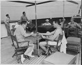 Photograph of Gen. Harry Vaughan and Gen. Robert Landry playing cards on the after deck of the U.S.S. WILLIAMSBURG... - NARA - 199034.tif