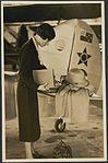 Portrait of aviator Jean Batten, near tail of aeroplane (15669871893).jpg