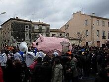 Une foule promenant un gros cochon rose en carton pâte lors d'un carnaval à Poussan