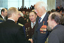 A man in the center, facing the left, is wearing medals on a jacket. He is shaking hands with another man, watched by three others.