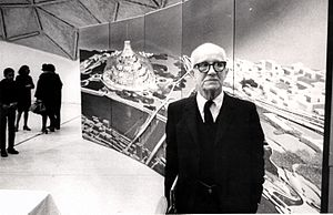 Old Man River's City project - R. Buckminster Fuller stands in front of a depiction of his domed city design at its first public showing at a community meeting in East St. Louis, Illinois.