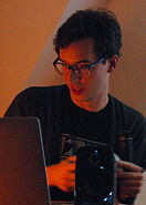 Bédard is holding an obfuscated controller while looking down and left at a computer screen. He has short, dark hair, medium-sized glasses, and wears a black t-shirt. The image has a warm palette and is grainy from the low light conditions.