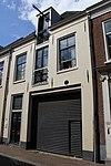 Huis bestaande uit twee bouwlagen met kap loodrecht op de straat en een kelder