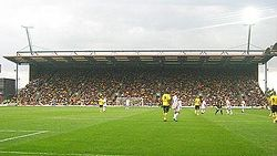 Several men standing on a grass football pitch. One is wearing a black top, black shorts and black socks. Four are wearing yellow tops, black shorts and yellow socks, and six are wearing white shirts, white shorts and white socks. The stand of a sports stadium is visible in the background, with floodlights rising behind it. The floodlights are brightly lit, and the sky is grey.