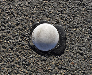 Botts' dots - A round, white Botts' dot, surrounded by excess adhesive