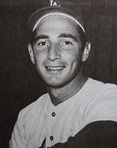 A black-and-white photograph of a smiling man pictured from the chest up; he is wearing a white baseball jersey and dark-colored baseball cap