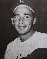 A man in a white baseball jersey and dark baseball cap smiles.