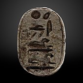 Small greyish oval seal with hieroglyphs on it.