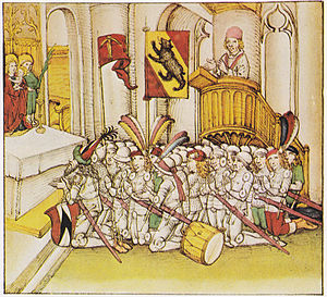 Rudolf von Erlach (1299–1360) - Rudolf von Erlach as field commander of Berne kneeling in prayer before the battle of Laupen 1339 (illustration from Spiezer Chronik, c. 1485). Rudolf is shown with his family coat or arms and wearing a pointed hat with his heraldic colours.