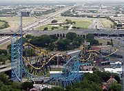 "Aerial view of ""Gotham City""-themed section of the park. SH 360 and I-30 intersect in the immediate background which show the proximity of the park to local roadways."