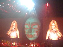 A large green coloured face with red markings is being projected onto a large screen. On both the sides of the face, a woman with long blonde hair is singing with a mic in her hand.