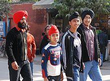 """Sikh-Familie: Der Vater und der ältere Sohn tragen den traditionellen Turban, die jüngeren Söhne den für Jungen üblichen """"Patka"""", der aus einem Stück Stoff besteht."""