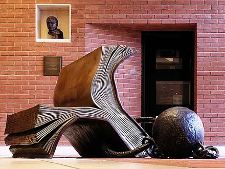 Bronze sculpture. Bill Woodrow's 'Sitting on History' was purchased for the British Library by Carl Djerassi and Diane Middlebrook in 1997. Sitting on History, with its ball and chain, refers to the book as the captor of information which we cannot escape  The bust visible top left is Colin St. John Wilson RA by Celia Scott, 1998 a gift from the American Trust for the British Library. Sir Colin designed the British Library building Sitting on History (1995) by Bill Woodrow, British Library, London, UK - 20061031.jpg
