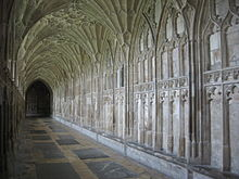 View along a stone cloister passage showing the conically shaped sections of the vault, and the carved stone panelling of the walls.