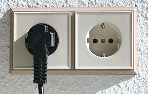 Double Schuko socket with one plug inserted. T...