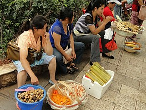 Yunnan cuisine - Street vendors. From bottom-left: quail eggs, two types of vinegar preserved vegetables (probably radish), bamboo rice (竹饭 zhufan), barbequed Jianshui tofu, roasted corn.