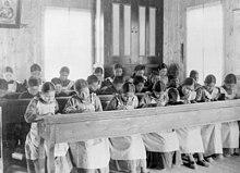 Inheemse kinderen werken aan lange bureaus