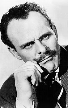 Terry-Thomas, wearing a dark jacket, looks off to the right, cuffing his moustache