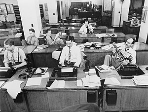 Newsroom - Reporters write at typewriters, receive information by telephone from field reporters, wait for assignments, and study various newspapers at desks in the newsroom of The New York Times, in this photo from 1942