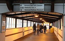 The overbridge in York station with signage for York Campus.jpg