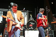 Photograph of a group singing and playing instruments on stage.