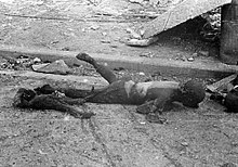 Black and white photograph of two burnt human bodies