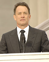 A colored photograph of a man wearing a grey blazer, with a black tie and white shirt. He is standing on a podium with a microphone positioned below his face.