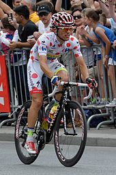 Rafał Majka wearing a white cycling jersey with red polka dots.