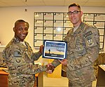 U.S. Air Force Chief Master Sgt. Kenneth Lindsey, left, the command chief master sergeant of the 455th Air Expeditionary Wing, presents the warrior of the week award to Tech. Sgt. Christopher Poole, with 131002-F-UR349-001.jpg
