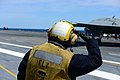 U.S. Navy Aviation Boatswain's Mate (Handling) 3rd Class Joshua Rabarabrokate salutes a Navy X-47B Unmanned Combat Air System demonstrator aircraft aboard the aircraft carrier USS George H.W. Bush (CVN 77) 130514-N-TB177-541.jpg