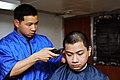 U.S. Navy Ship's Serviceman Seaman Recruit Sam Suprana gives a haircut to Machinist's Mate Fireman Apprentice Luis Plata in the barber shop aboard the aircraft carrier USS George H.W. Bush (CVN 77) in 130523-N-CZ979-044.jpg
