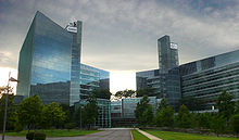 Two geometric all glass towers connected by a central atrium stand in front of a grassy walkway and under a dark and cloudy sky