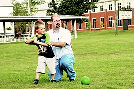 Un jeune garçon avec une batte de base-ball, son père assis à ses côtés modifie son geste