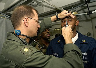 Flight surgeon - A deployed U.S. Navy flight surgeon performs a shipboard exam in the Persian Gulf in 2004.