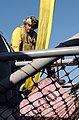 US Navy 041104-N-1638B-034 Airman John Stroub performs safety checks on safety nets surrounding the flight deck of USS Ronald Reagan (CVN 76).jpg