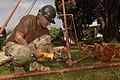 US Navy 051226-N-4374S-018 Hospital Corpsman 1st Class Michael McCune, assigned to Naval Mobile Construction Battalion Three (NMCB-3), cuts an old swing set.jpg