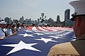 US Navy 060529-N-4936C-002 Marines, Sailors, Soldiers, Airmen, Coast Guardsmen and military veterans display the American flag during the playing of taps on the deck of the museum and display ship USS Intrepid.jpg