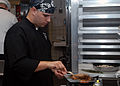US Navy 060825-N-3973P-004 Culinary Specialist 3rd Class Steven Mize grills a steak for the Iron Chef competition held on board Naval Base Kitsap.jpg