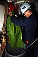 US Navy 071114-N-1513W-039 Gunner's Mate Seaman Marshall Dunn holds a plastic bag as a water chute while draining a fire plug to be removed and replaced.jpg
