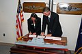 US Navy 080214-N-0923G-001 Susan Tomaiko, left, and Brian Cuccias, vice president and DDG 1000 program manager for Northrup Grumman Shipbuilding, sign the $1.4 billion construction contract for the DDG 1000 Zumwalt Class destro.jpg